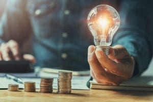 Man holds illuminated light bulb next to stacks of coins