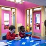 Two children make something using paper in their classroom. The walls behind are bright pink.