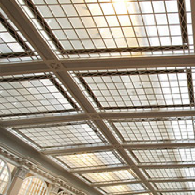 The inside of a former factory that has lots of glass on both the walls and ceiling